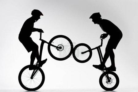 Photo pour Silhouettes des motards du procès spectacle stunt synchrone sur blanc - image libre de droit