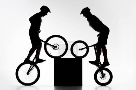 silhouettes of trial bikers performing stunt with cube synchronously on white