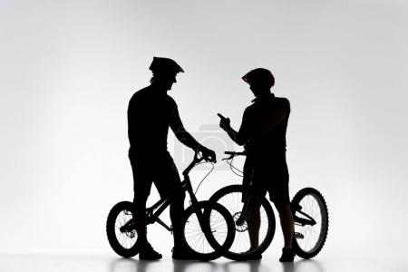 silhouettes of trial bikers with bicycles chatting on white