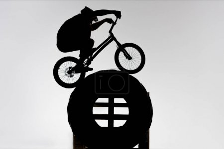silhouette of trial cyclist balancing on tractor wheel on white