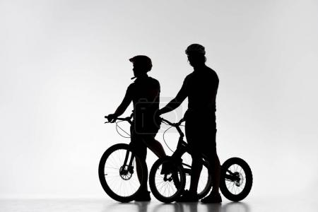 silhouettes of trial bikers in helmets with bicycles on white