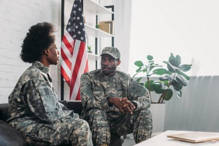 Woman and man in army uniform talking on sofa at home