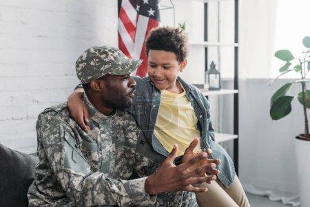 Foto de African american boy abrazar y escuchar a su padre en uniforme del ejército - Imagen libre de derechos