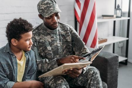 Father in army uniform and african american boy reading book