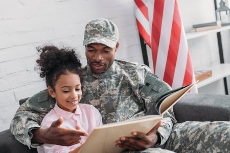 Male soldier reading book to his daughter