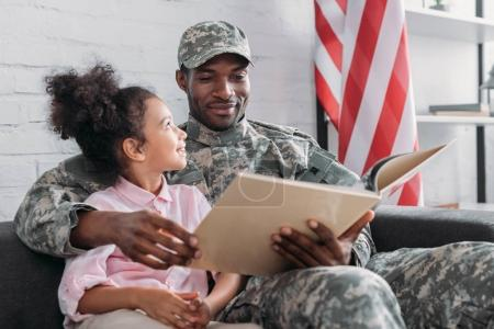 African american male soldier with daughter reading book