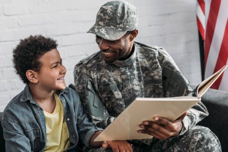African american man in camouflage clothes and boy reading book