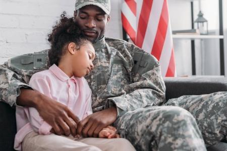 Father in army uniform and african american child embracing at home