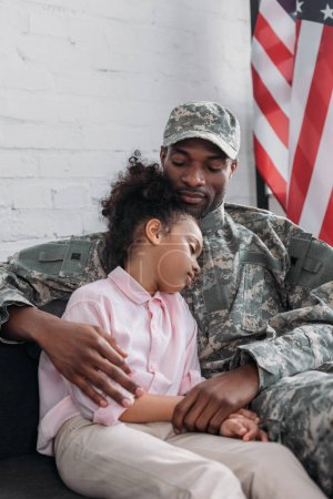 Army soldier father looking at his sleepy daugher