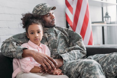 Father in army uniform hugging african american daughter