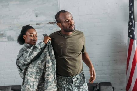 African american female soldier helping man to get dressed in camouflage clothes