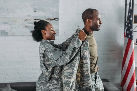 Female soldier helping man to get dressed in camouflage clothes