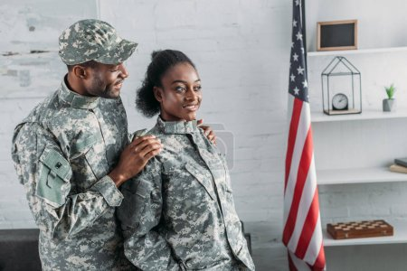African american male soldier embracing woman in camouflage clothes
