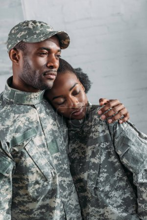 Woman and man in army uniform hugging at home