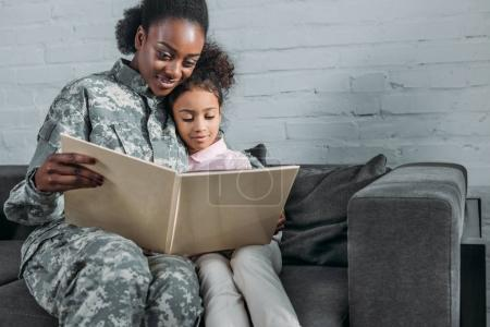 African american woman in camouflage clothes and child reading book