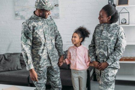 Woman and man in army uniform with their daughter