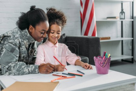 Mother army soldier and her daughter drawing together