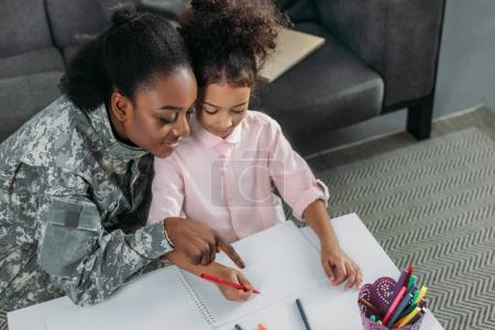 African american woman in camouflage clothes and child drawing together