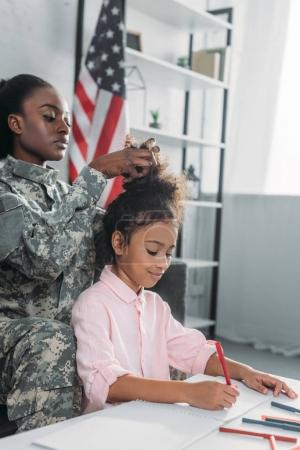 African american female soldier fixing hairstyle of daughter busy with drawing by table