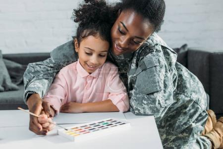 African american female soldier with daughter drawing with watercolor paint