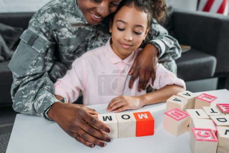 Mother soldier and african american child playing words game