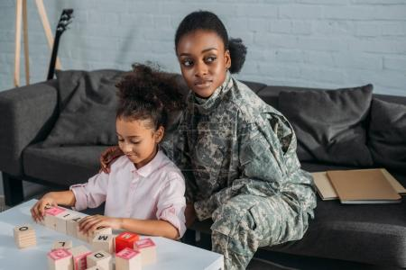 African american female soldier with daughter playing words game