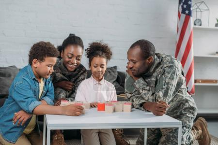 Woman and man in army uniform with their children playing words game