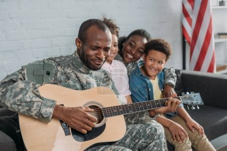 African american woman and children listening to father in camouflage clothes playing guitar