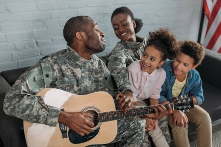African american female soldier and kids listening to father in camouflage clothes playing guitar