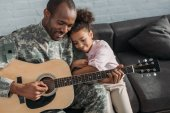 Smiling soldier playing guitar and hugging daughter