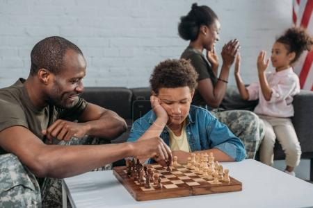 Young army soldier man playing chess with his son while mother and daughter playing together