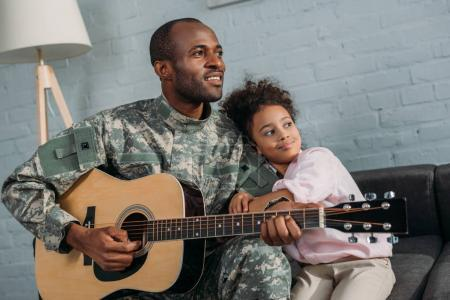 Father in army uniform playing guitar and hugging daughter