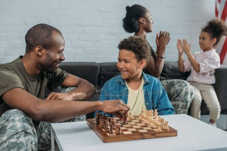Smiling soldier playing chess with his son while mother and daughter playing together