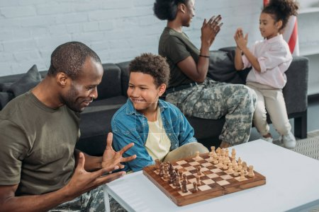 Man in camouflage clothes teaching his son to play chess while mother and daughter playing together