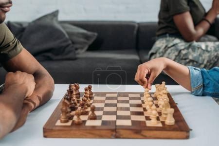 African american father playing chess with his son