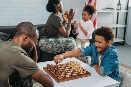 Father in army uniform playing chess with his son while mother and daughter playing together