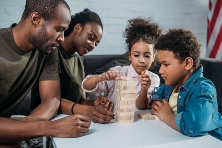 Parents in camouflage clothes with their children playing wooden blocks game