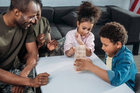 Woman and man in army uniform with their children playing wooden blocks game