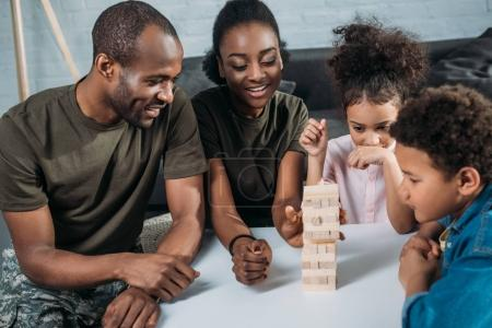African american female and male soldiers with their children playing wooden blocks game