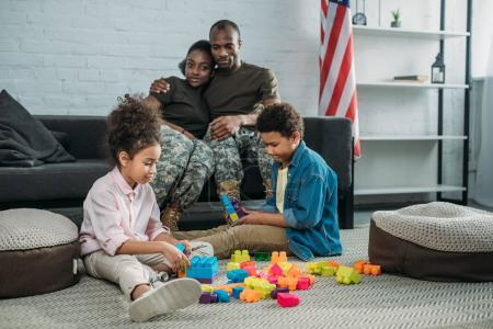Parents in camouflage clothes looking at their children playing with cubes