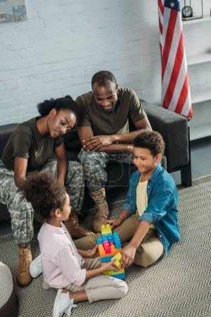 Woman and man in army uniform looking at their children playing with constructor