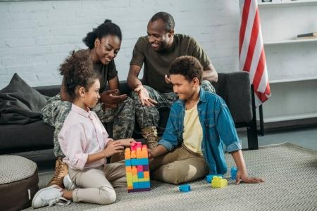 African american man and woman soldiers looking at their children playing with cubes