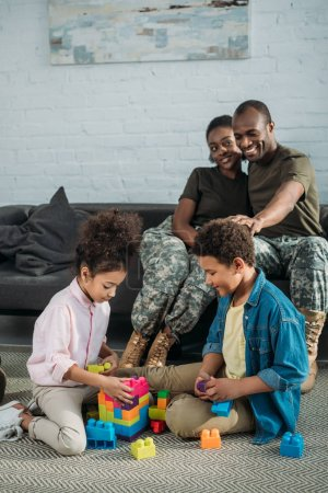 African american female and male soldiers looking at their children playing with cubes