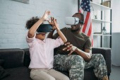 Young male soldier in camouflage clothes and little daughter using vr glasses