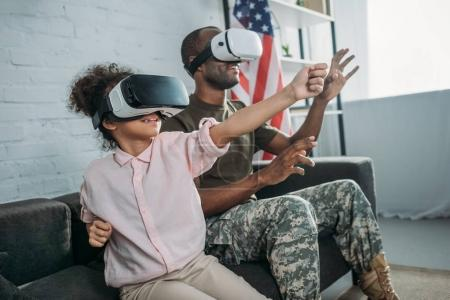 Father in army uniform and african american daughter using vr glasses