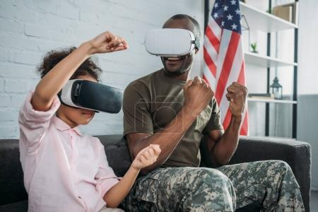 Photo for Happy family with daughter and father in army clothes playing with virtual reality headsets - Royalty Free Image