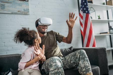 Army soldier father in vr glasses by his daughter