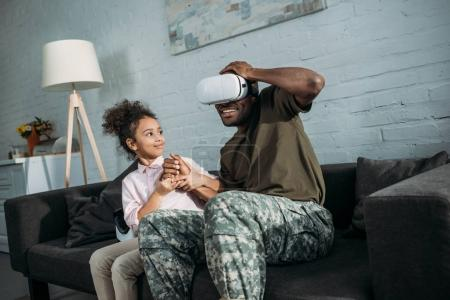 Father in army uniform with african american daughter using vr glasses