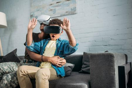 Mother soldier and african american boy using virtual reality headsets