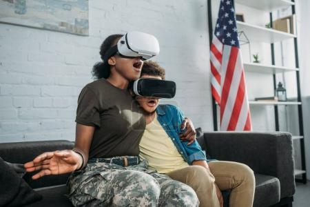 African american female soldier with son using vr glasses